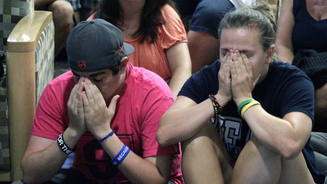 Andrew Hanselman, left, of Bucks County, Pa., and Maddy Pryor, a senior, from Neptune, N.J., react as they listen to a television in the HUB on the Penn State University main campus in State College, Pa., as the NCAA sanctions against the Penn State University football program are announced Monday, July 23, 2012.  The NCAA slammed Penn State with an unprecedented series of penalties Monday,  including a $60 million fine and the loss of all coach Joe Paterno's victories from 1998-2011, in the wake of the Jerry Sandusky child sex abuse scandal. (AP Photo/Gene J. Puskar)
