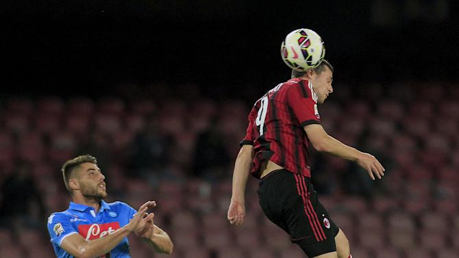 AC Milan's Destro jumps for the ball as Napoli's Lopez watches during their Italian Serie A soccer match at the San Paolo stadium in Naples