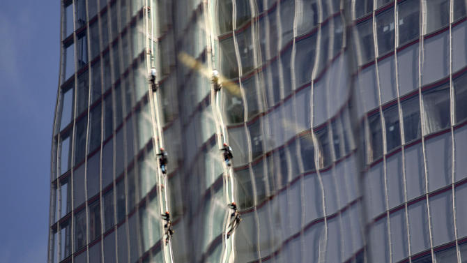 Reflected in a nearby building, Greenpeace protesters climb up The Shard, the tallest building in western Europe, during a protest against the oil company Shell's drilling in the Arctic, Thursday, July 11, 2013. (AP Photo/Sang Tan)