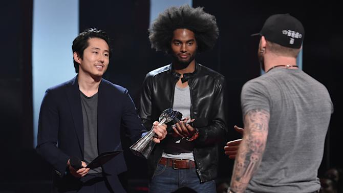 Brantley Gilbert, right, accepts the renegade award from Steven Yeun, left, at the iHeartRadio Music Awards at The Shrine Auditorium on Sunday, March 29, 2015, in Los Angeles.  (Photo by John Shearer/Invision for iHeartRadio/AP Images)