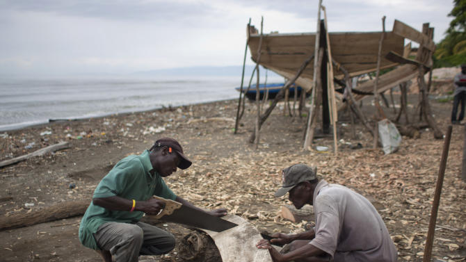 In this May 4, 2013 photo, boat builders saw a piece of wood as they build a sailboat on the beach of Leogane, Haiti. The 30-foot-long boats are purchased by smugglers for around $12,000 and then taken to northern Haiti to find passengers.  Hundreds of Haitian migrants have made their way to the U.S. territory of Puerto Rico in recent months, finding that if they can get to Puerto Rico without getting arrested, it's relatively easy to fly on to U.S. cities such as Miami, Boston or New York without even having to show a passport. (AP Photo/Dieu Nalio Chery)