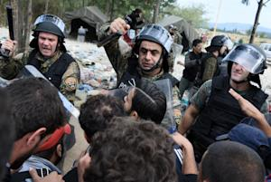 Macedonian policemen scuffle with refugees and migrants…