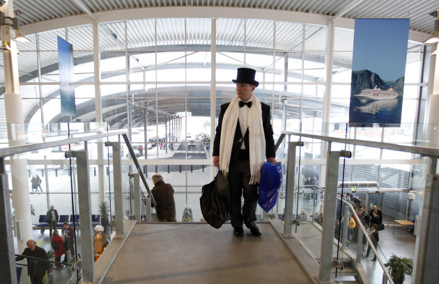 A passenger in evening dress  hurries as he goes to check in for the MS Balmoral Titanic memorial cruise in Southampton, England, Sunday, April  8, 2012. Nearly 100 years after the Titanic went down,