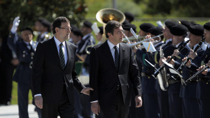 Spain's Prime Minister Mariano Rajoy, left, walks with Portugal's Prime Minister Pedro Passos Coelho, centre, as they review troops during a welcome ceremony, prior to a meeting, at the Moncloa Palace, in Madrid, Monday, May 13, 2013. (AP Photo/Andres Kudacki)