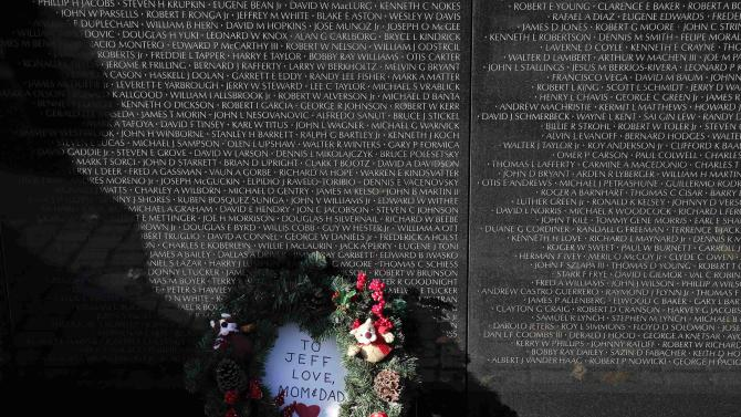 A holiday wreath is left at the U.S. Vietnam Veterans Memorial underneath names on the wall in Washington