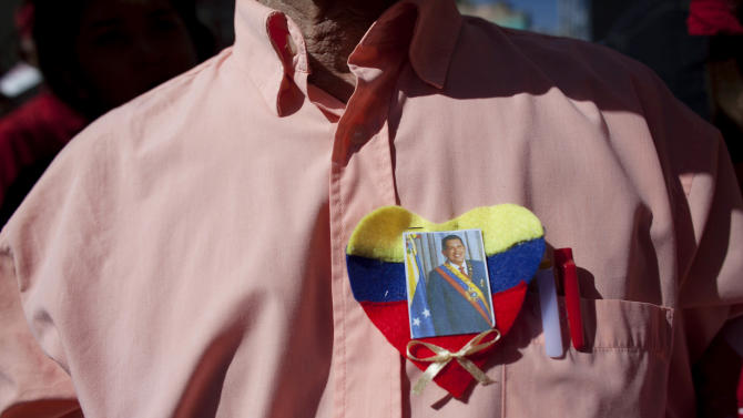 "A supporter of  Venezuela's President Hugo Chavez dons a heart-shaped felt pin with the image of the South American leader at a rally in Caracas, Venezuela, Thursday, Jan. 10, 2013.  Hundreds of supporters gathered outside his presidential palace in an alternative inauguration, showing their support for the ailing leader and wearing T-shirts with the slogan ""I am Chavez.""  The government organized the rally for the cancer-stricken leader on the streets outside Miraflores Palace on what was supposed to be his inauguration day. A swearing-in ceremony has been indefinitely postponed, despite opposition complaints. (AP Photo/Ariana Cubillos)"