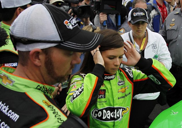 Danica Patrick, center, prepares to get in her car before the start of the NASCAR Daytona 500 Sprint Cup Series auto race at Daytona International Speedway, Sunday, Feb. 24, 2013, in Daytona Beach, Fl