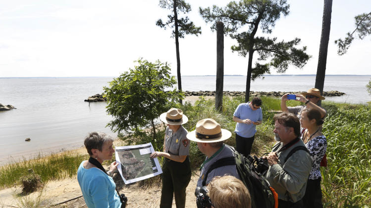 In this Thursday June 5, 2014 photo, US Secretary of the Interior Sally Jewell, left, tours Jamestown Island in Jamestown, Va. Jewell toured Jamestown to highlight climate change's threat to the first permanent European settlement in America. A power company's plan to build high-rise transmission towers within sight of Jamestown Island has stirred opposition from historic preservationists who say they'll be a visual blight from the swampy shore where America sprouted. (AP Photo/Steve Helber)