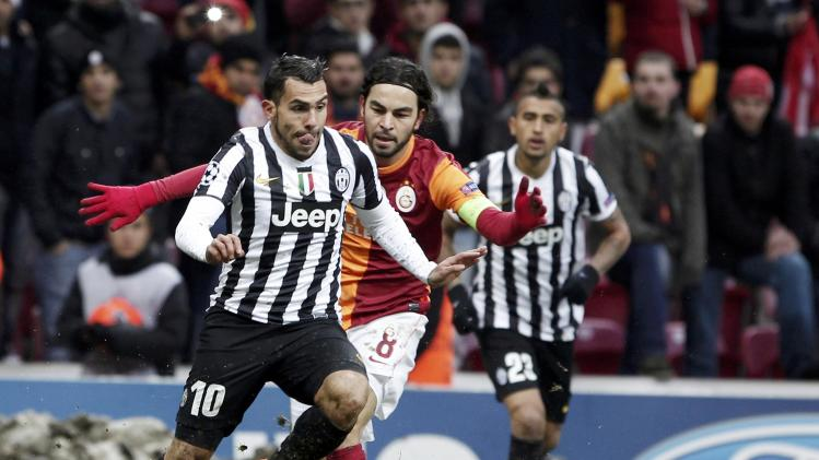 Tevez of Juventus challenges Inan of Galatasaray during their Champions League soccer match in Istanbul