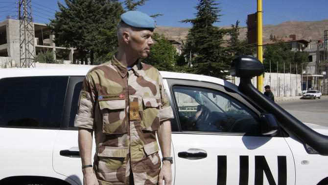 FILE - In this Sunday, May 20, 2012 file photo, Norwegian Maj. Gen. Robert Mood, head of the U.N. observer team in Syria, stands near a U.N. observers car in Zabadani neighborhood in Damascus, Syria. U.N. observers in Syria suspended their activities and patrols Saturday, June 16, 2012 because of escalating violence in the country, the head of the mission said, the strongest sign yet that an international peace plan for Syria is disintegrating. Maj. Gen. Robert Mood said rising bloodshed over the past 10 days was posing significant risks to the lives of the some 300 observers in the country, and was impeding their ability to carry out their mandate.(AP Photo/Muzaffar Salman, File)
