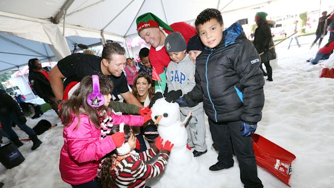 """IMAGE DISTRIBUTED FOR MATTEL - Bryan Stockton, Mattel CEO, WWE star Diva Eve, WWE star The Miz, and Los Angeles school children race against the clock to attempt to break the Guinness World Record for most snowmen built in one hour at Mattel's Southern California headquarters during the annual """"Mattel 12 Days of Play"""" on Thurs., Dec. 13, 2012 in El Segundo, Calif. (Photo by Casey Rodgers/Invision for Mattel/AP Images)"""