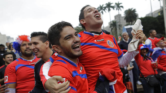 Costa Rica soccer fans celebrates a goal as they watch the Italy vs. Costa Rica World Cup match inside the FIFA Fan Fest area in Sao Paulo, Brazil, Friday, June 20, 2014. (AP Photo/Nelson Antoine)