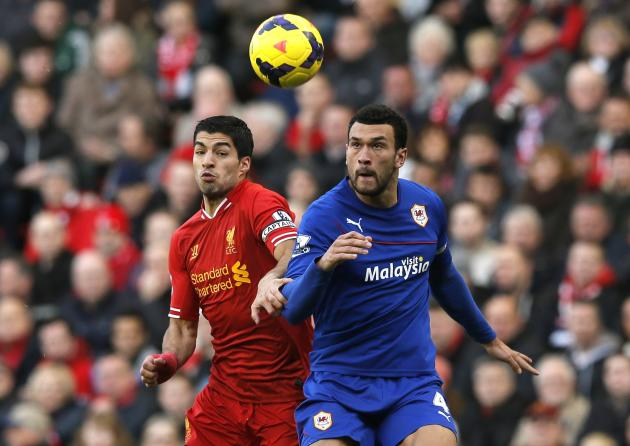 Liverpool's Suarez challenges Cardiff City's Caulker during their English Premier League soccer match at Anfield in Liverpool