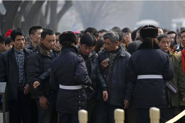 Police officers scan and check the identification of visitors entering the Tiananmen Gate in Beijing