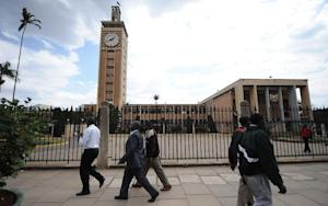 Kenyans walk past the parliament building in Nairobi …