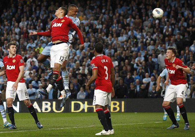 Manchester City's Vincent Kompany, 3rd left, scores against Manchester United during their English Premier League soccer match at The Etihad Stadium, Manchester, England, Monday, April 30, 2012. (AP P