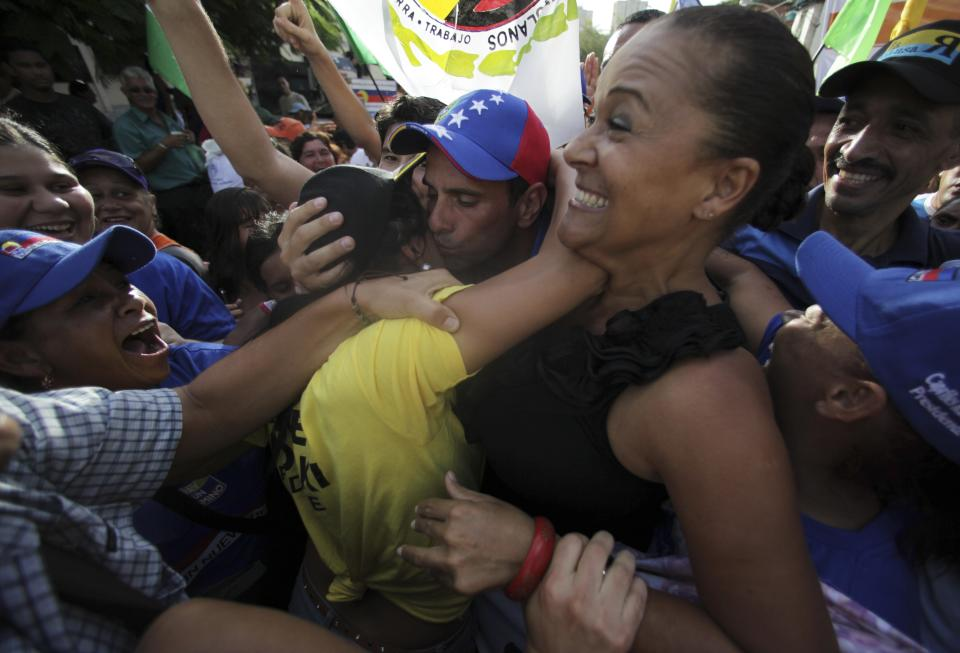 Venezuela's presidential candidate Henrique Capriles, center, kisses a supporter as he arrives for a campaign rally in Catia La Mar, Venezuela, Friday, Aug. 3, 2012. Venezuela's presidential election is scheduled for Oct. 7. (AP Photo/Fernando Llano)