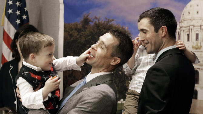FILE - In this Feb. 27, 2013 file photo, Dr. Paul Melchert, left, gets interrupted by son, Emmett, as he attempts to address the media while his partner James Zimerman, right, holds twin, Gabriel, during a news conference in St. Paul, Minn., where lawmakers introduced a bill to legalize gay marriage in Minnesota. On Thursday, March 21, 2013, the American Academy of Pediatrics, the most influential U.S. pediatrician's group, endorsed gay marriage, saying a stable relationship between parents regardless of sexual orientation contributes to a child's health and well-being. (AP Photo/Jim Mone, File)