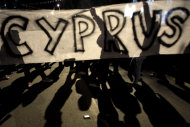 <p>               Protesters hold a banner during an anti- bailout rally outside of European Union house in capital Nicosia, Cyprus, Sunday, March 24, 2013. After failing for a week to find a solution to a crisis that could force their country into bankruptcy, Cypriot politicians turned to the European Union on Sunday in a last-ditch effort to help the island nation forge a viable plan to secure an international bailout. (AP Photo/Petros Karadjias)