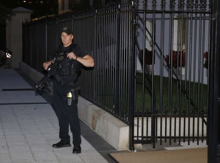 An armed U.S. Secret Service agent with an automatic rifle guards the White House complex during an evacuation over a security alert moments after U.S. President Barack Obama and his family left for the presidential retreat, Camp David, in Maryland