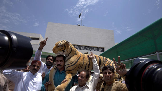 Supporters of Pakistan's upcoming Prime Minister Nawaz Sharif carry a stuffed animal, which was the election symbol of Sharif's party, outside the National Assembly building in Islamabad, Pakistan, Wednesday, June 5, 2013. Pakistan's parliament is set to elect Sharif as prime minister on Wednesday, completing a historic transition of power in the country's coup-riddled history. (AP Photo/Anjum Naveed)