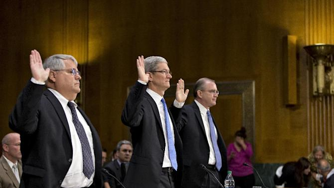 Apple CEO Tim Cook, center, flanked by Peter Oppenheimer, Apple's chief financial officer, left, and Phillip A. Bullock, Apple's head of Tax Operations, are sworn in on Capitol Hill in Washington, Tuesday, May 21, 2013, prior to testifying before the Senate Homeland Security and Governmental Affairs Permanent subcommittee on Investigations hearing to examine the methods employed by multinational corporations to shift profits offshore and how such activities are affected by the Internal Revenue Code. Apple, the world's most valuable company, based in Cupertino, Calif., holds a billion dollars in an Irish subsidiary as a tax strategy, according to a report issued this week by the subcommittee.  (AP Photo/J. Scott Applewhite)