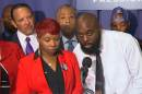 In this image from video the parents of Michael Brown, Lesley McSpadden and Michael Brown, Sr., speak at a news conference with civil rights leaders at the National Press Club Thursday, Sept. 25, 2014 in Washington. Brown's parents were joined by Eric Garner's mother in calling for full federal investigations into the death of their sons, two unarmed black men who died in police encounters. (AP Photo/AP Video)