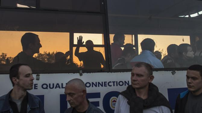 A member of the pro-Russian rebels, who is a prisoner-of-war (POWs), waves from inside a bus as he waits with others to be exchanged, north of Donetsk, eastern Ukraine