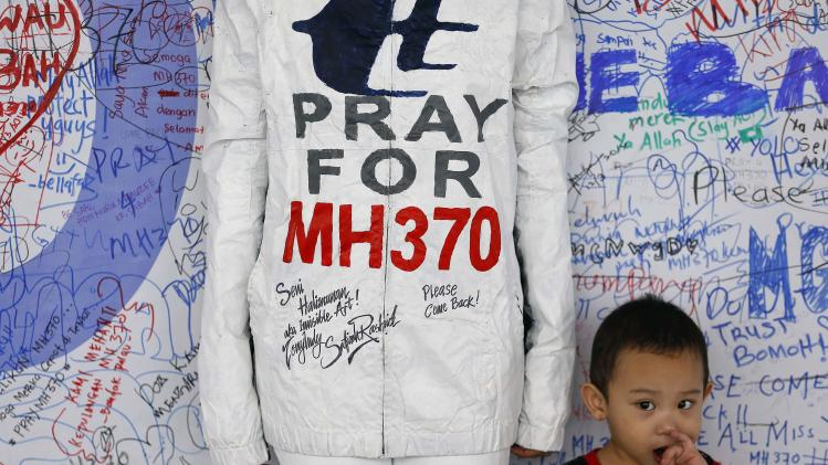A boy stands beside a model posing for pictures during an art performance in support for the passengers of the missing Malaysia Airlines MH370 at the departure hall of the Kuala Lumpur International Airport