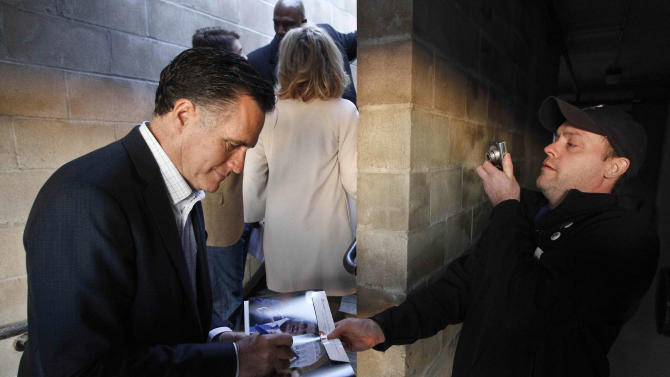 In this Dec. 28, 2011 file photo, Mitt Romney signs an autograph during a campaign stop at Elly's Tea and Coffee in Muscatine, Iowa. (AP Photo/Chris Carlson)