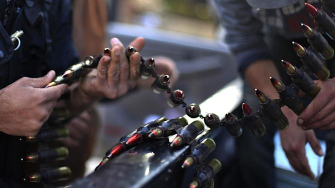 Syrian fighters check their ammunition during clashes with Syrian army forces in the town of Harem, on the outskirts of Idlib, Syria, Saturday, Nov. 17, 2012. (AP Photo/ Khalil Hamra)