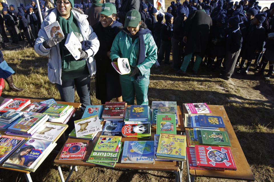 Women interact before handing out books during birthday celebrations for former South African President Nelson Mandela in Mvezo, South Africa, Wednesday, July 18, 2012. Across the country, and even abroad, people are doing good deeds to honor the country's most famous statesman on his 94th birthday today. (AP Photo/Schalk van Zuydam)