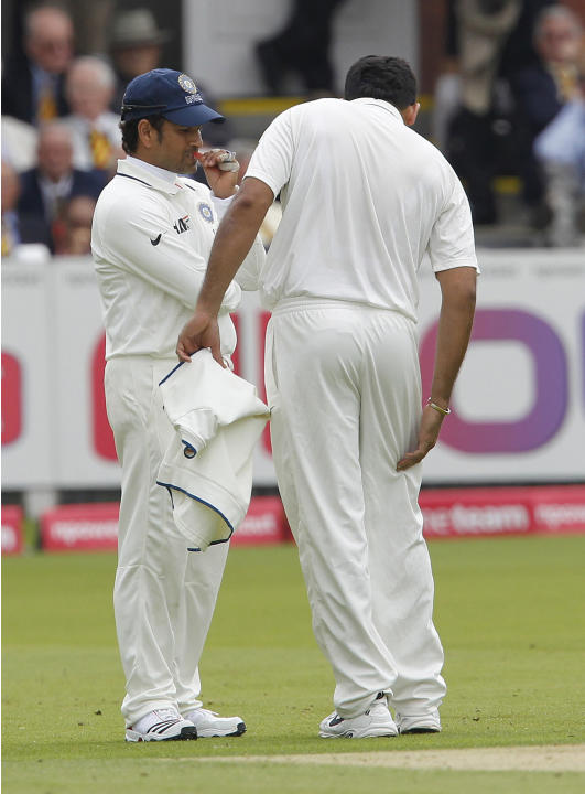 India's Zaheer Khan (R) leaves the field holding his leg as India's Sachin Tendulkar (L) gestures during Day 1 of the first test match between England and India at Lord's Cricket Ground in