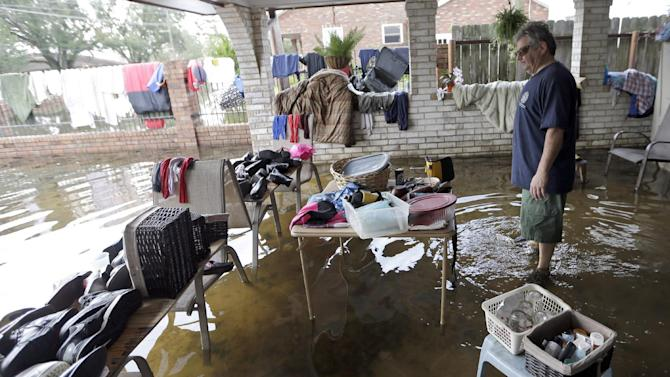 Peter Roccaforte looks over some of his belongings set out to dry as he stands in floodwaters from Hurricane Isaac at his home in Reserve, La., Saturday, Sept. 1, 2012. Floodwaters cover many streets and power remains out in some areas. Louisiana's Public Service Commission said more than 443,000 customers remained without electricity around Louisiana on Saturday morning, days after Hurricane Isaac crept across the state.  (AP Photo/David J. Phillip)