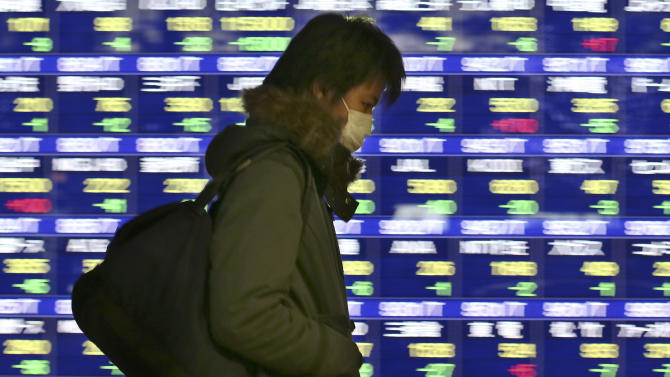 A man walks by an electronic stock board of a securities firm in Tokyo Monday, Dec. 16, 2013. Most Asian markets fell Monday as the Nikkei 225 index slipped 1.6 percent to 15,152.91. (AP Photo/Koji Sasahara)