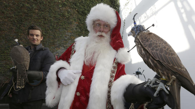Actor Brady White portrays Santa Claus as he holds a falcon included in the Bespoke Global Falconry Companion experience offered in the Neiman Marcus Christmas Book Tuesday, Oct. 8, 2013, in Dallas. The gift is listed at $150,000. (AP Photo/LM Otero)