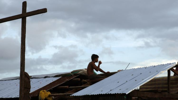 A typhoon survivor drinks coffee as he takes a break from rebuilding the roof of his typhoon damaged house in Tacloban city