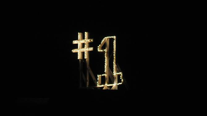 The No. 1 sign is lit on the Notre Dame campus, Sunday, Nov. 18, 2012, in South Bend, Ind. A tradition linked to Notre Dame becoming the No. 1 football team in the country is the lighting of the sign atop of a former student dormitory on the campus. Notre Dame was last ranked No. 1 in 1993. The NCAA college football team, ranked No. 1 in both polls and by the computer ratings, needs only to beat slumping rival Southern California on Saturday, Nov. 24 in Los Angeles to earn its first trip to the BCS title game.  (AP Photo/Joe Raymond)