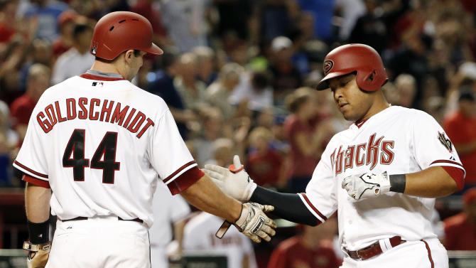 Arizona Diamondbacks' Yasmany Tomas, right, slaps hands with Paul Goldschmidt (44) after hitting a two-run home run against the Los Angeles Dodgers during the sixth inning of a baseball game Monday, June 29, 2015, in Phoenix. (AP Photo/Ross D. Franklin)