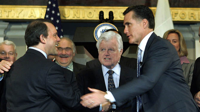 FILE - In this April 12, 2006, file photo, Massachusetts Gov. Mitt Romney, right, shakes hands with Massachusetts Health and Human Services Secretary Timothy Murphy after signing into law a landmark bill designed to guarantee that virtually all Massachusetts residents have health insurance, at Faneuil Hall in Boston, as  Sen. Edward Kennedy, D-Mass., stands at center. Romney pushed for the requirement, but now says health care mandates should be left to the states, not the federal government. (AP Photo/Elise Amendola, File)