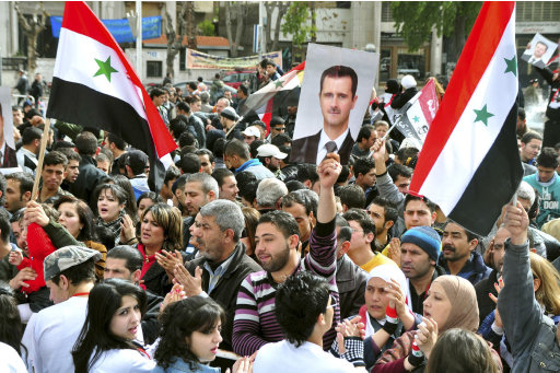 People attend a rally to show support for Syria's President Bashar al-Assad in Damascus