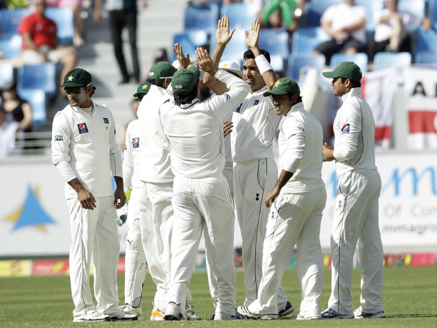 Pakistan's Umar Gul, third right, celebrates with his teammates taking the wicket of England's Jonathan Trott, not pictured, during the first day of the third cricket test match of a three match serie