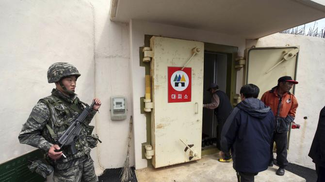 A South Korean marine stands guard as residents evacuate to a shelter on Socheong Island, near the border with North Korea