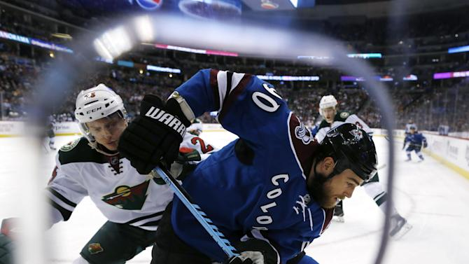 Colorado Avalanche center Ryan O'Reilly, front, digs the puck out of the corner as Minnesota Wild defenseman Jonas Brodin, of Sweden, defends in the first period of an NHL hockey game Saturday, Feb. 28, 2015, in Denver. (AP Photo/David Zalubowski)