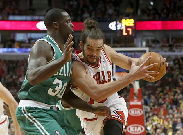 Chicago Bulls center Joakim Noah, right, drives against Boston Celtics forward Brandon Bass during the second half of an NBA basketball game on Thursday, Jan. 2, 2014, in Chicago. The Bulls won 94-82