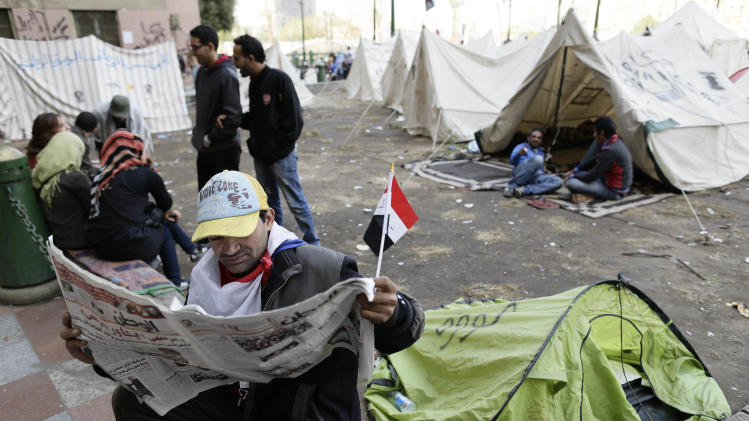 An Egyptian protester reads the newspaper as other sit next to their tents in Tahrir Square in Cairo, Egypt, Sunday, Dec. 9, 2012. Egypt's liberal opposition has called for more protests on Sunday after the president made concessions overnight that fell short of their demands to rescind a draft constitution going to a referendum on Dec. 15. (AP Photo/Hassan Ammar)