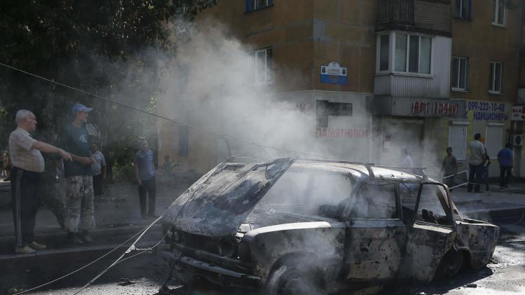 People look at a burned car with the bodies of victims killed by what locals say was recent shelling by Ukrainian forces in Donetsk, eastern Ukraine