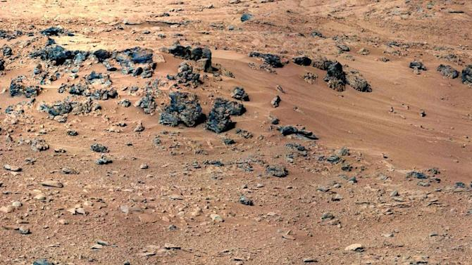 This handout image provided by NASA, taken Sept. 28, 2012,  is a mosaic of images taken by the telephoto right-eye camera of the Mast Camera before the rover arrived at Rocknest. Mars Curiosity is about to sip its initial taste of the red planet's sand. But first, NASA's rover has to play bartender to make sure the dry dust is shaken, not stirred.The rover's scoop will dig into the sand Saturday. Then the action starts. Mission sampling chief Daniel Limonadi said the end of the rover's arm will shake vigorously and noisily for eight hours, like a Martian martini mixer gone mad. That will vibrate the fine dust grains through the rover chemical testing system to cleanse it of unwanted residual Earth grease. (AP Photo/NASA)