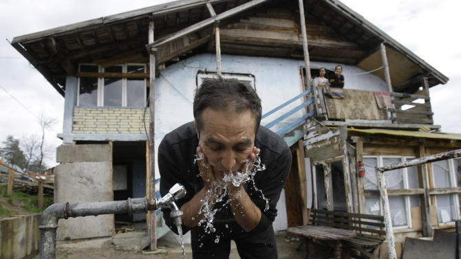 The unexpected  movie star, Nazif Mujic, washes his face in front of his home in the village of Poljice,150 kms northeast of Sarajevo, on Wednesday, April 10, 2013.  People in the Gypsy village  of Poljice say they will never forget the night they almost fell off their chairs two months ago. Did they really hear the elegant woman on TV correctly? Could she really be talking about their neighbor, the toothless man who passed his days selling scrap metal and lived in the shack down the road? The camera switched to a frightened-looking Najif Mujic. Yes it was him. THEIR Nazif _ who had just left Matt Damon and Jude Law in the dust to win the best actor award at the Berlin Film Festival.    (AP Photo/Amel Emric)