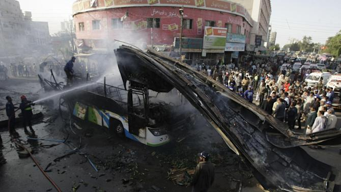 Firemen try to extinguish a fire following a blast in Karachi, Pakistan, Saturday, Dec. 29, 2012. The blast that ripped through the bus set the vehicle on fire and reduced it to little more than a charred skeleton, killing scores of people and leaving many injured. Authorities were trying to determine whether the explosion was caused by a bomb or a gas cylinder, said a police spokesman. (AP Photo/Fareed Khan)